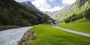 Langs elva opp til Buer gard med fonn og fjell i bakgrunn.